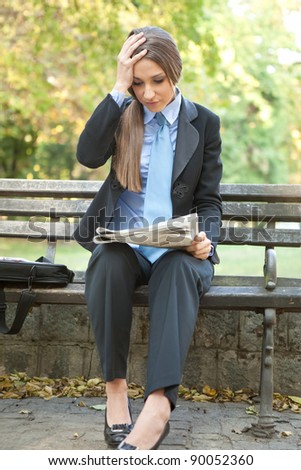 disappointed businesswoman holding her head and reading bad  news