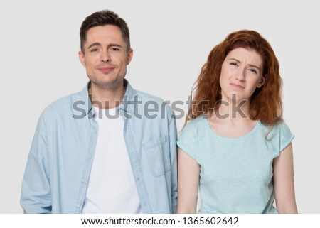 Disappointed millennial man and woman in casual clothes isolated on grey studio background unhappy hearing bad news, upset guy and girl feel down or sad, have problems or unpleasant life experience Stock photo ©