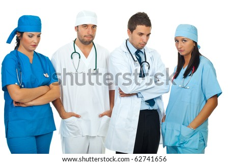 Disappointed team of different doctors standing in a row and looking down or at camera isolated on white background