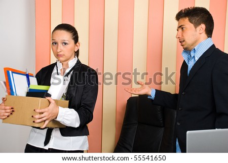 Disappointed woman  holding box with  belongings is fired by her boss and invited to leave the office