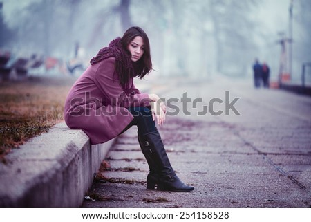 Disappointing Young Woman is Sitting in Depression on the Stone Parapet in the Gloomy Autumn Day