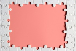 disassemble incomplete white jigsaw puzzle pieces with plain pink empty space.