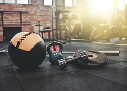 Disassembled barbell, medicine ball, kettlebell, dumbbell lying on floor in gym. Sports equipment for workout with free weight. Functional training