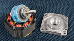 Disassembled electric step motor parts on a dark grid background. Blue rotor with steel shaft on black stator with electromagnetic coils and copper wire winding. Aluminum cast of ball bearing housing.
