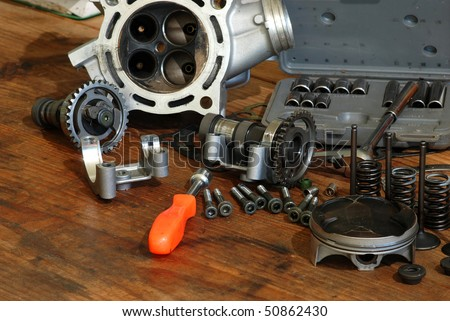 Disassembled four-stroke Motorcycle engine of motocross bike scattered on old wooden workbench.  Socket set and nut driver included.