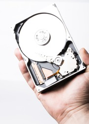 Disassembled hard disk drive in male hand on white background
