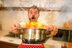 disaster home cook at kitchen- young funny and desperate man in cooking apron holding pot in flames in stress and fear making a mess of fire and smoke with food burning