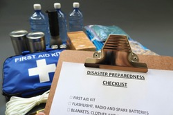 Disaster preparedness checklist on a clipboard with disaster relief items in the background.Such items would include a first aid kit,flashlight,tinned food,water,batteries and shelter.Disaster plan.