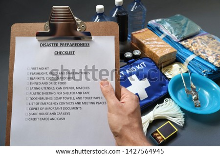 Disaster preparedness checklist on a clipboard with disaster relief items in the background.Such items would include a first aid kit,flashlight,tinned food,water,batteries and shelter.