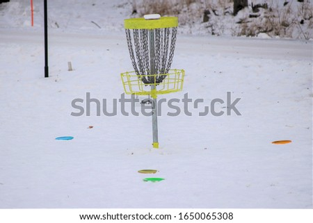 Disc golf basket and discs in snow