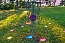 Disc golf basket with discs inside and outside.