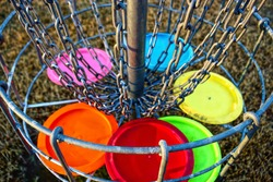 Disc golf basket with discs. The metal parts of the basket are selectively in focus.