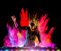 Disc jockey brunette girl mixing electronic music with colored powder explosion on background