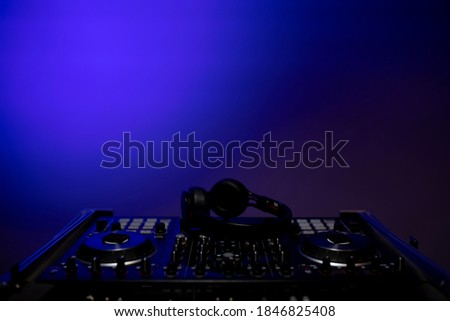 Photo of  Disc jockey console in the club with pulsating and psychedelic lights. Nightclub and music concept. Close up shot. Space for graphic designer