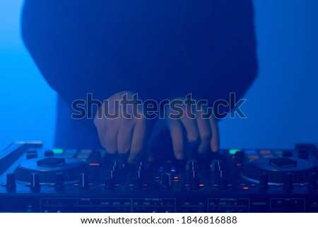 Photo of  Disc jockey in the club with pulsating and psychedelic lights. Nightclub and music concept. Close up shot