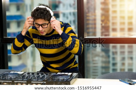 Disc jockey man or DJ in the casual sweater is wearing headphones stand behind sound mixing console, Doing sound check before the party began.