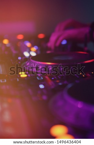 Disc jockey mixes tracks on techno music festival in nightclub.Professional dj playing musical tracks on popular entertainment event in club.Musician mixing songs on party