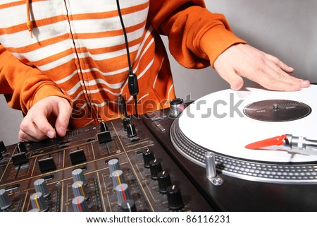 Disc jockey playing hip-hop music on professional top-class club equipment