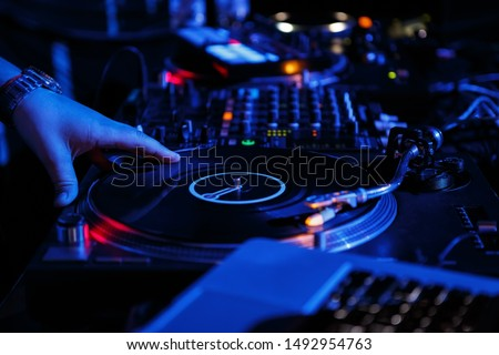Disc jockey scratches vinyl records on turntable.Professional hip hop dj plays musical tracks on rap concert scene in bright blue neon lights.Retro stage audio equipment