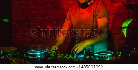 Disc jockey with cropped head in fashion grey t-shirt playing music on turned on and lightning dj deck in cafe club restaurant under color spot lights with red brick wall and a little green leaf near