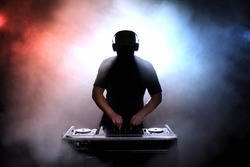 Disc jokey, DJ, silhouette over foggy illuminated background