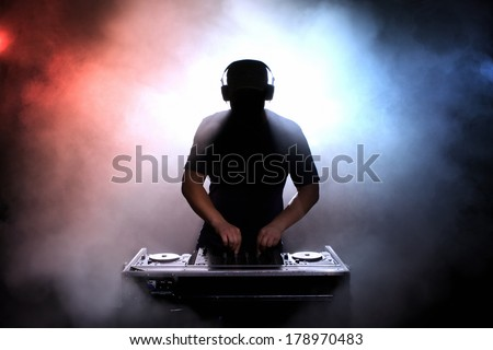 Disc jokey, DJ, silhouette over foggy illuminated background
