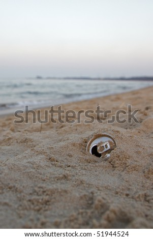 Discarded aluminum can in the sand - sea and sky