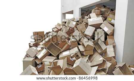 Discarded brown colored corrugated paper carton boxes overflowing from a recycle refuse chamber, isolated against white.