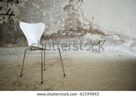 Discarded building interior with white chair. - stock photo