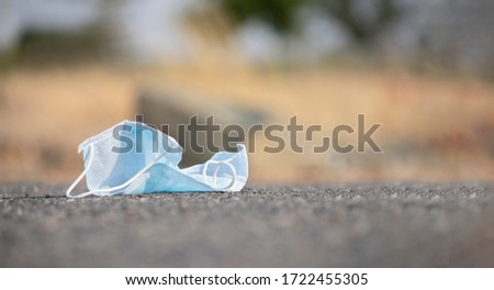 Discarded medical face mask stuck into road - concept of unhygienic dispose of masks helps to spread covid-19 or coronavirus. Stock photo ©
