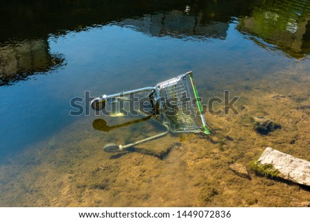 discarded shopping trolly thrown in canal littering the landscape vandals