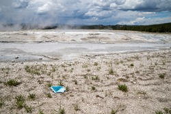 Discarded surgical face mask covering thrown in the fountain paint pots geysers and geothermal features of lower geyser basin in Yellowstone National Park during COVID-19 pandemic. Garbage and litter