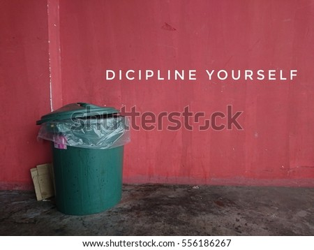 discipline yourself with dustbin on red background wall