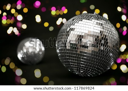 Disco ball and evening ornament over black background with lights