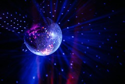Disco ball scatters blue light in a dark room