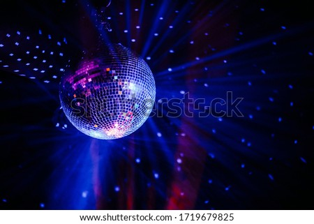 Photo of  Disco ball scatters blue light in a dark room