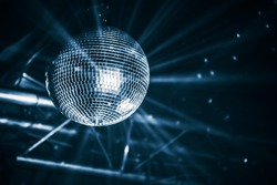 Disco ball with bright rays, blue toned night party background photo