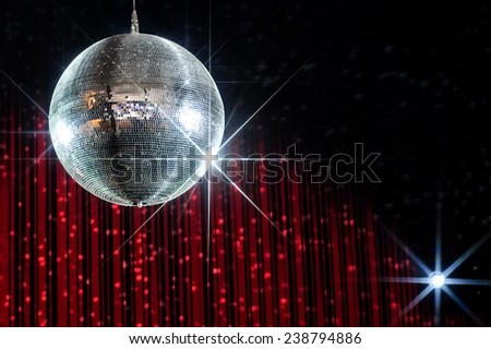 Disco ball with stars in nightclub with striped red and black walls lit by spotlight