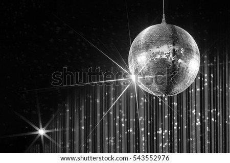 Disco ball with stars in nightclub with striped white and black walls lit by spotlight, party and nightlife entertainment industry