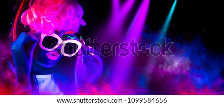 Disco dancer in neon light in night club Fashion model woman in neon light, portrait of beautiful girl with fluorescent make-up, Body Art design in UV, painted face, sunglasses, colorful make up