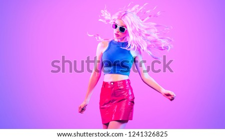 Disco Party Doll girl with Purple hairstyle Having Fun dance. Music vibrations. High Fashion. Young Gorgeous model woman in glamour vinyl skirt. Colorful neon Light. Night Clubbing