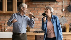 Disco 60s. Overjoyed older senior husband wife having fun sing song at kitchen hold imaginary microphones of tools utensils. Energetic creative aged spouses listen to music enjoy karaoke funny cooking