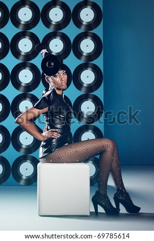 Disco woman on the chair with vinyl records on the wall