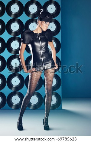 Disco woman with vinyl records on the wall