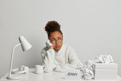 Discontent Afro American woman in eyewear feels tired and lonely, looks aside, cannot achieve necessary goal, poses at white desktop with desklamp, papers, headphones, fatigue after paperwork