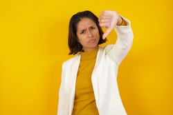 Discontent European woman shows disapproval sign, keeps thumb down, expresses dislike, frowns face in discontent, dressed in white shirt, isolated over gray background. Body language concept.