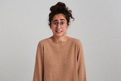 Discontent lady, unsure woman with dark curly hair bun. Wearing beige jumper and glasses. Emotion concept. Shrugs and wry face. Watching at the camera isolated over white background