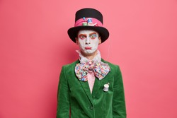 Discontent man dressed in halloween costume has professional makeup purses lips with offended expression poses indoor over rosy background. Halloween event or festival concept. Character of wonderland