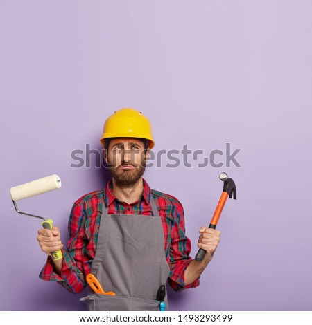 Discontent man wears protective hardhat, apron, holds painting roller and hammer, busy with house rennovation, holds labor tools, stands against purple studio wall with blank space. Manual worker
