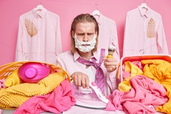 Discontent redhead man looks with sulking expression applies foaming gel on cheeks going to shave irons laundry has busy day woke up late does domestic responsibilities isolated over pink wall